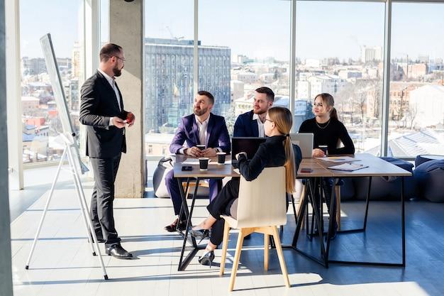 Уверенный бизнесмен делает презентацию нового проекта в зале заседаний на собрании компании