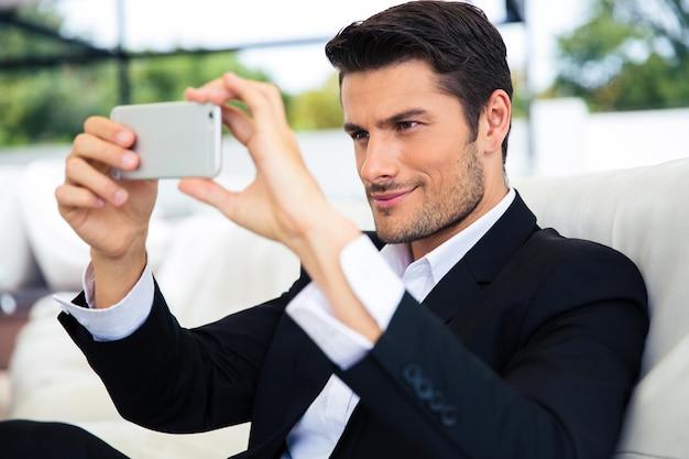Уверенный бизнесмен, делающий селфи фото на смартфоне в ресторане