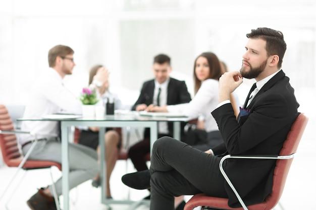 Уверенный бизнесмен на фоне офиса