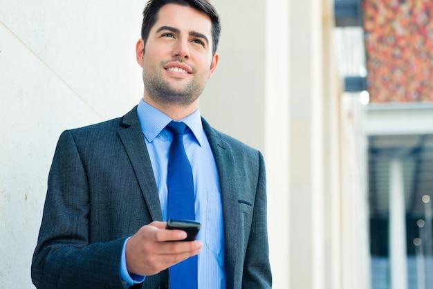 Confident businessman outdoor using phone