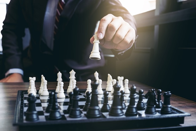 Confident businessman playing chess game