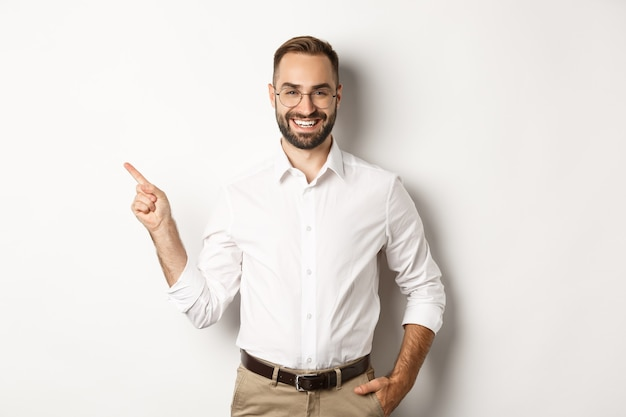 Confident businessman pointing finger left at company logo, standing over white background.
