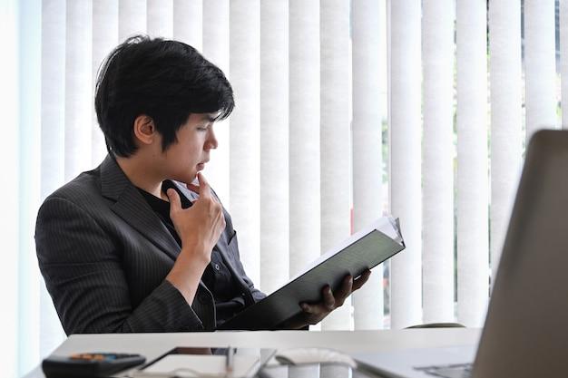 Уверенно бизнесмен, читая бизнес-отчет в офисе.