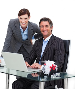 Confident businessman showing something on computer to his colle