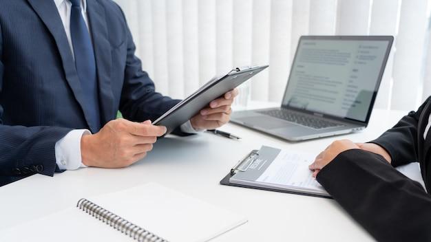 Уверенный бизнесмен, сидящий перед офис-менеджером, беседует с интервьюером с коллегой