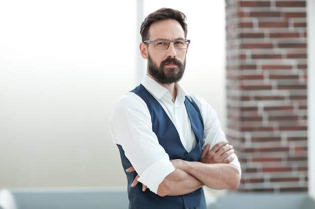 オフィスのロビーに立っている自信を持ってビジネスマン。コピースペース付きの写真