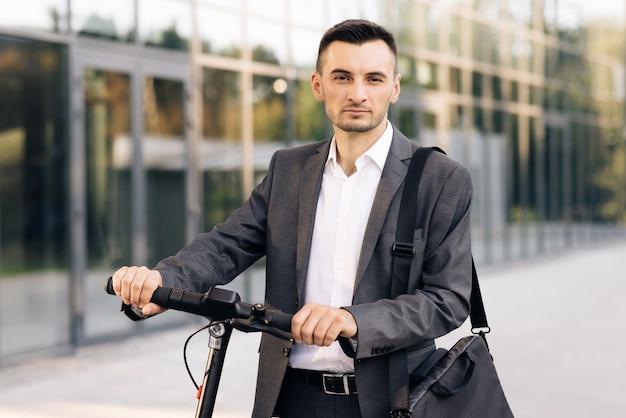 Уверенный бизнесмен, стоящий с электросамокатом и смотрящий на аренду райдера эскутера камеры