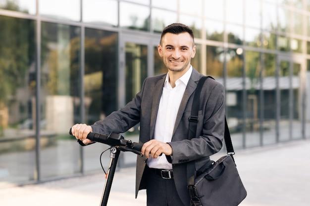 Уверенный бизнесмен, стоящий с электросамокатом и глядя в камеру, счастливый успешный бизнесмен