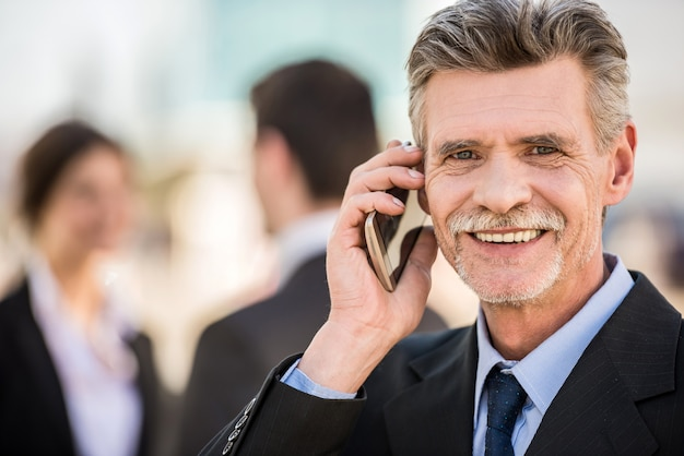 Confident businessman in suit talking on the phone.
