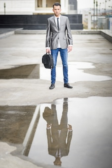 Confident businessman surrounded by puddles