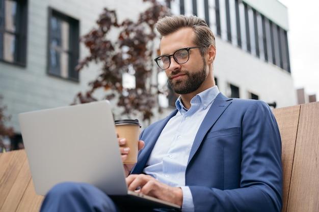職場で座ってオンラインで働くラップトップコンピューターを使用して自信を持ってビジネスマン