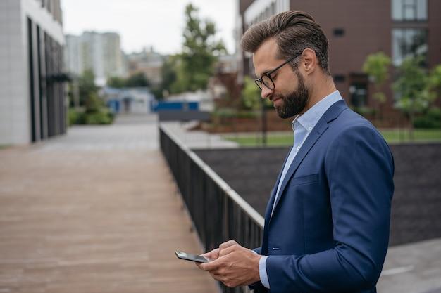 Уверенный бизнесмен, использующий мобильный телефон, рабочее общение онлайн, стоя на улице