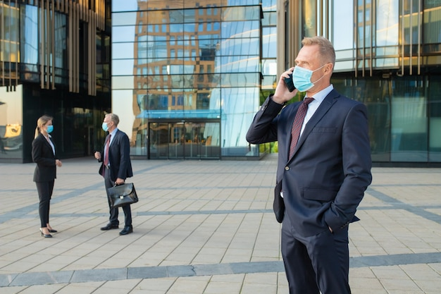 Confident businessman wearing mask and office suit talking on cellphone outdoors. businesspeople and city building glass facade in background. copy space. business and epidemic concept