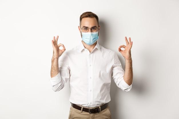 Fiducioso uomo d'affari che indossa la mascherina medica e mostrando segni di approvazione, sfondo bianco.