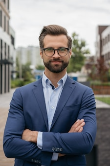 Confident businessman wearing suit stylish eyeglasses standing on the street successful business