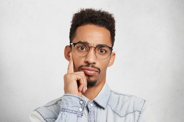 Fiducioso uomo d'affari indossa gli occhiali, tiene il dito sul mento mentre ascolta attentamente la presentazione aziendale dei colleghi
