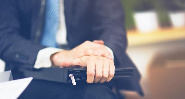 Уверенный бизнесмен с папкой в руках в офисе
