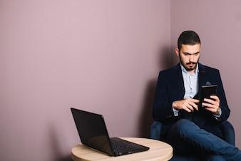 Confident businessman with gadgets