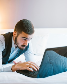 Confident businessman with laptop on bed