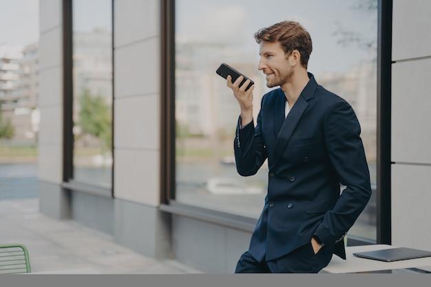 Уверенный бизнесмен со смартфоном, используя приложение голосового помощника, опираясь на столик в кафе на открытом воздухе