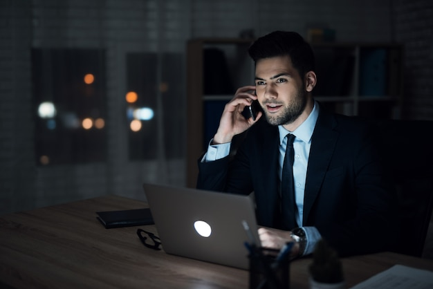Confident businessman working in office at night