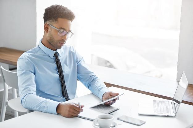 彼のラップトップに取り組んでいる自信の実業家