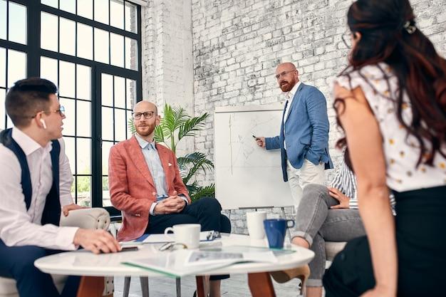 フリップチャートに自信を持ってビジネスマンが会議室の会社の会議で新しいプロジェクトを提示する