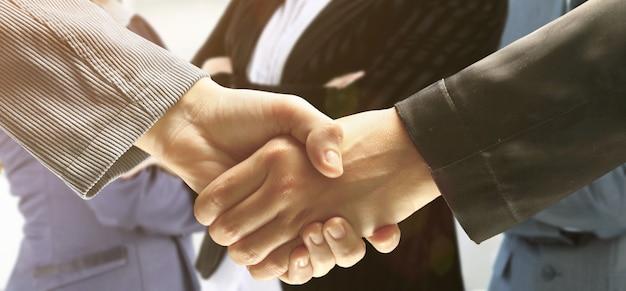 ビジネスパートナーの背景に握手する自信のあるビジネスマン。