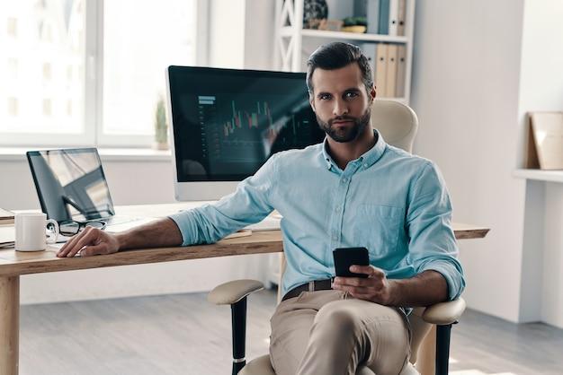 自信のあるビジネスマン。オフィスに座ってカメラを見ている若い現代実業家