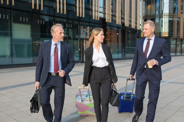 Uomini d'affari fiduciosi che viaggiano con i bagagli, camminano in hotel, fanno le valigie, parlano. vista frontale. viaggio d'affari o concetto di comunicazione aziendale