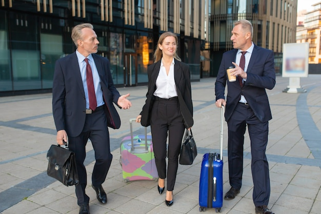 Confident businesspeople with luggage walking to hotel, wheeling suitcases, talking. full length, front view. business travel or corporate communication concept