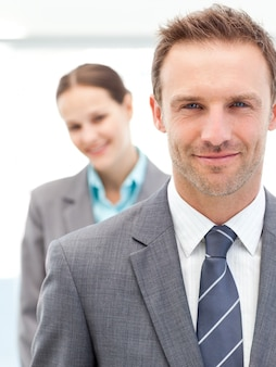 Confident businesswoman and businessman posing together in line