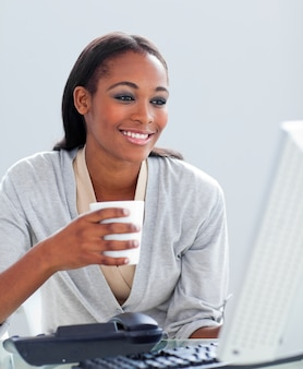 Confident businesswoman drinking a coffee at her desk