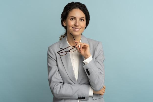 Уверенная деловая женщина, держащая очки, улыбаясь, глядя на камеру, позирует изолированной на синем фоне