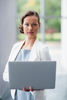 Confident businesswoman holding laptop at conference centre