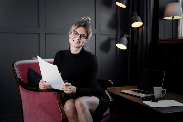 Confident businesswoman holding papers