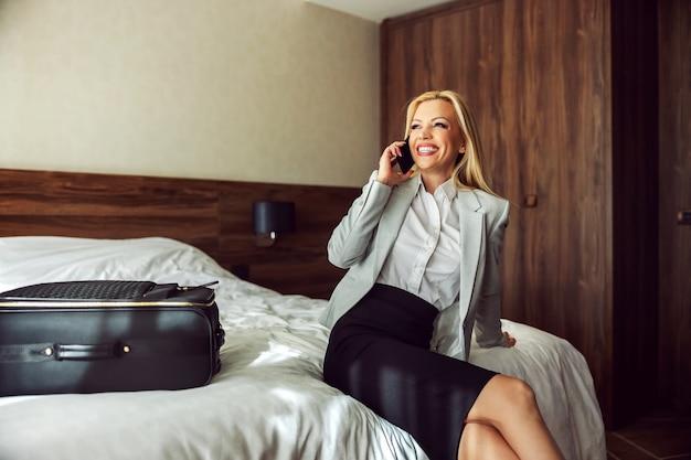 電話をしてホテルの部屋で微笑んでいる正装の自信のある実業家。彼女の隣には、ホテルをチェックアウトする準備をしている黒いスーツケースがあります。出張終了