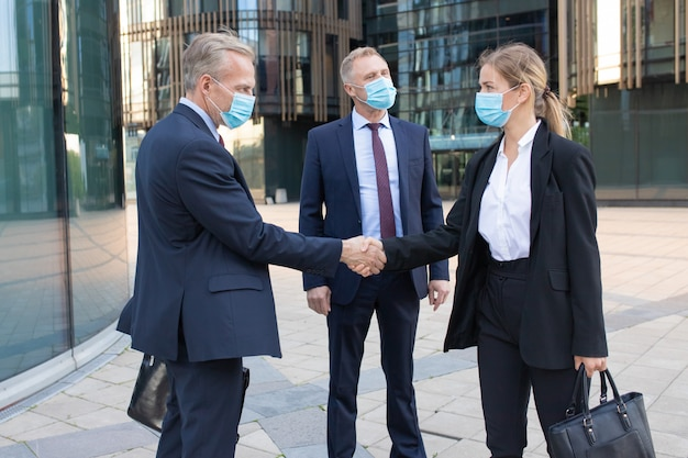 Confident businesswoman and middle-aged manager in facial masks handshaking outdoors. successful employers greeting on street and working during coronavirus pandemic. meeting and partnership concept