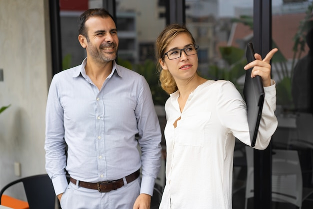 Confident businesswoman showing something to male colleague