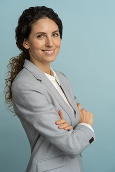 Confident businesswoman, smiling, looking at camera posing isolated on blue background.
