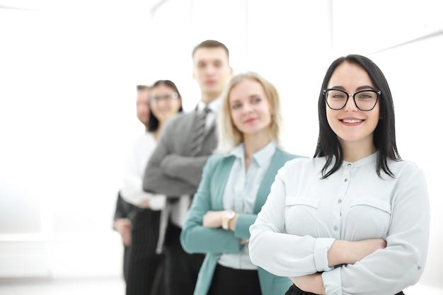 자신의 비즈니스 팀 앞에 서 있는 자신감 있는 사업가. 복사 공간이 있는 사진