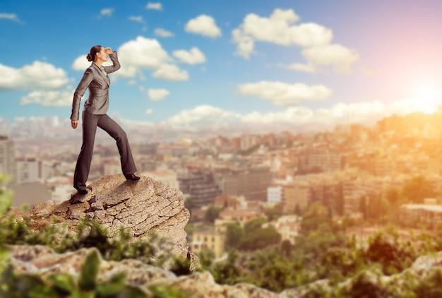 산 위에 서 있는 자신감 있는 사업가가 도시를 바라보고 있다