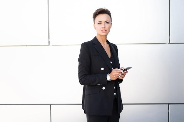 インターネットを使用して携帯電話で自信を持って女性実業家テキストメッセージメール