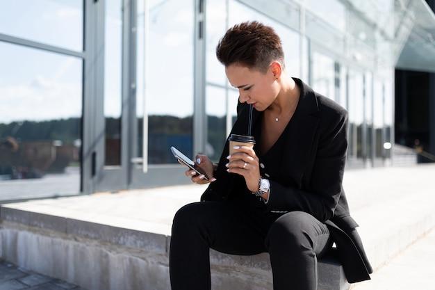 인터넷을 사용하여 핸드폰에 자신감 사업가 문자 메시지 이메일 편지