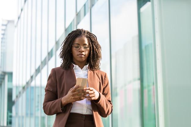 Confident businesswoman texting message