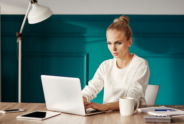 Confident businesswoman typing on laptop keyboard