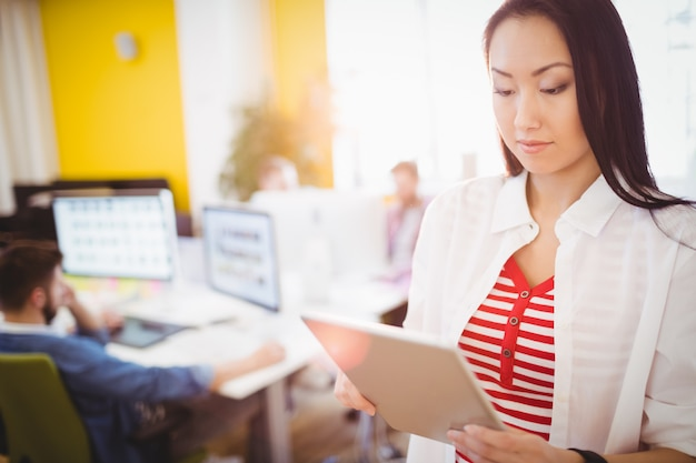 Confident businesswoman using digital tablet at creative office