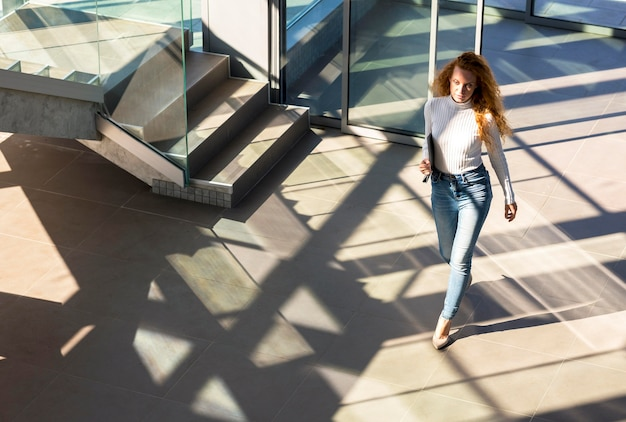 Confident businesswoman walking in the building long shot