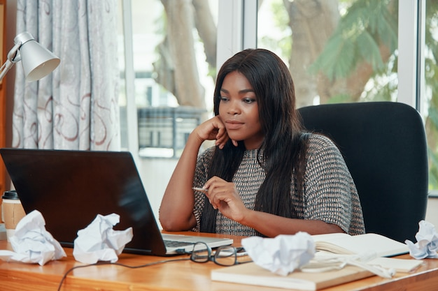Confident businesswoman watching laptop in office