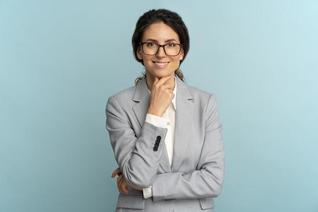 Уверенная деловая женщина носить очки, касаясь ее подбородка, улыбаясь, глядя на камеру, позирует изолированной на синем фоне.